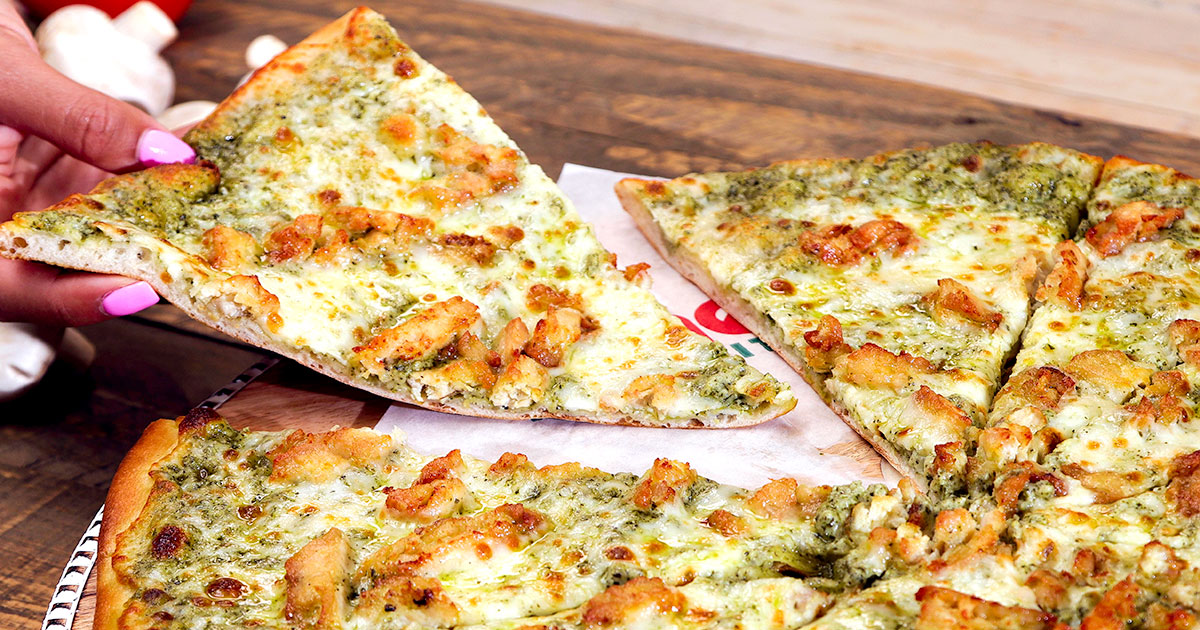 A slice of pizza topped with pesto and chicken being grabbed from a whole pie.