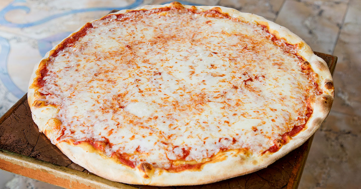 A large cheese pizza laying on a table.