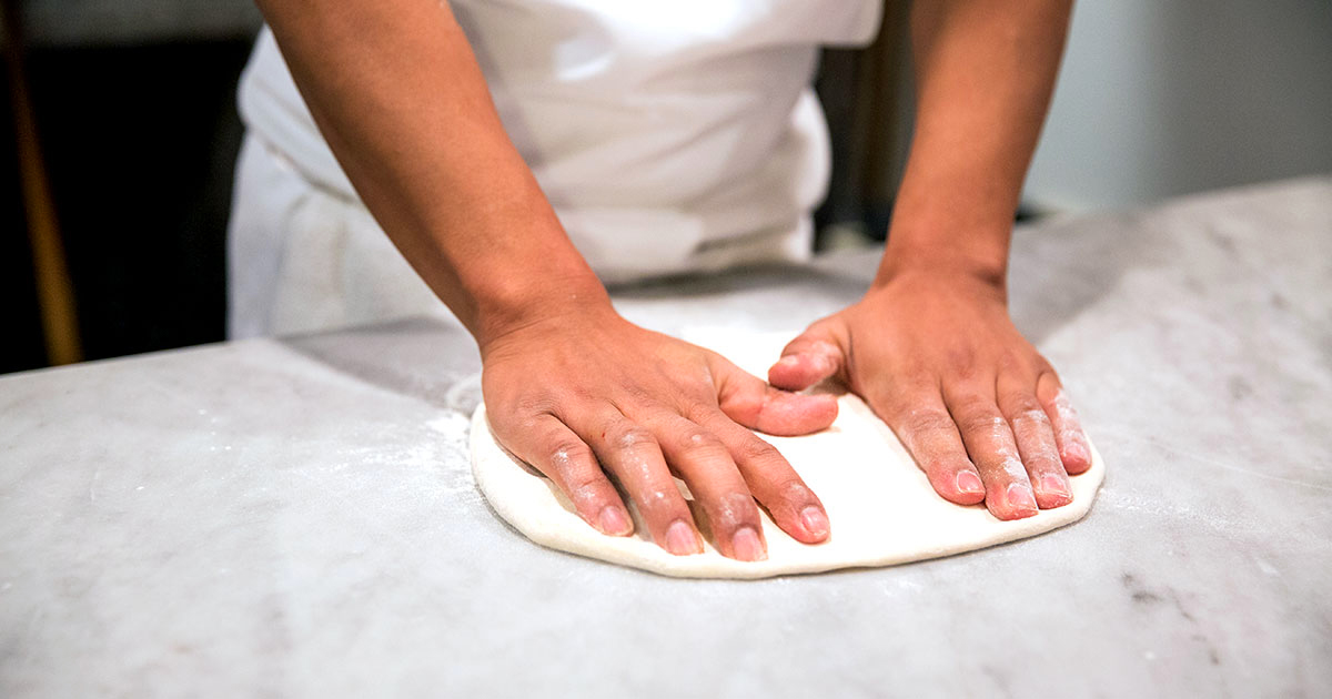 A ball of pizza dough being stretched by two hands.