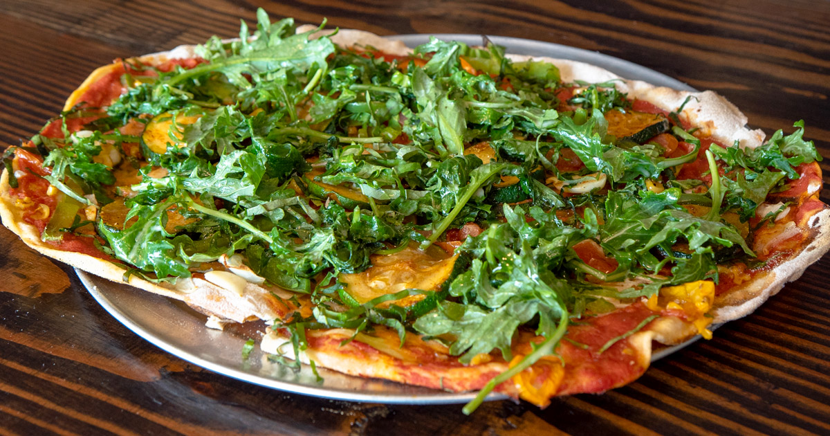 A top down shot of a vegan pizza covered in arugula and sauce.
