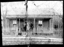 What appears to be a child and three adults, all African-American, on the porch of a Dallas home, undated.