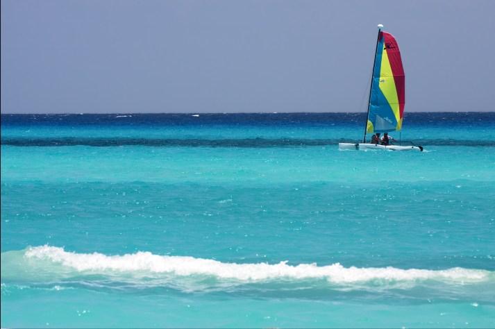 tropical lagoon hill navigable froth cloudy catamaran boat and coastline in mexico playa del carmen