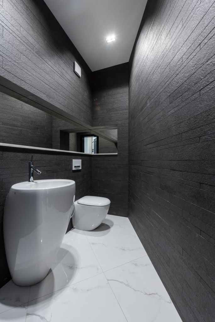 contemporary bathroom interior with dark stone walls and marble styled floor