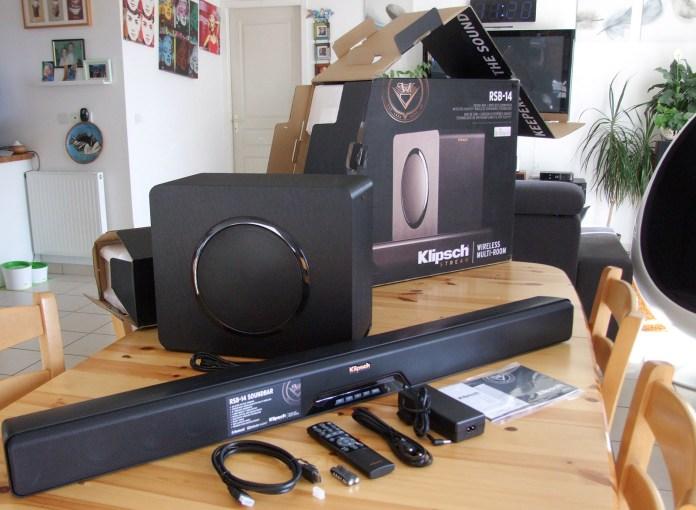 La barre de son Klipsch RSB-14 en impose dès le déballage ! Un câble HDMI fait partie de la dotation, ainsi qu'une télécommande infrarouge et ses piles. La haut-parleur de 20 cm monté sur le flanc droit du caisson est abrité derrière une grille métallique rehaussée d'un cerclage noir brillant.