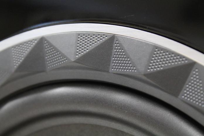 Le haut-parleur de grave de l'enceinte Elipson Prestige Facet 24F, avec membrane en papier traité et suspension à demi-rouleau en caoutchouc.