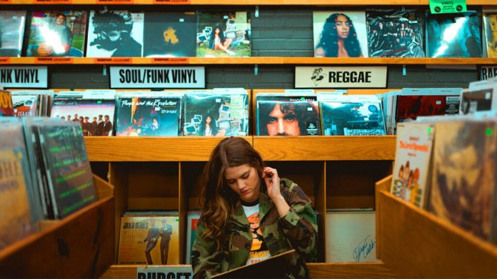 Girl in record store contemplating how to distribute her own music