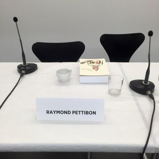 Sorgenvoll blickten die Journalisten anfangs auf den freigebliebenen Platz Pettibons und fragten sich einmütig, ob er wohl noch kommen würde, -- ... und er kam. Spät, aber er kam.
