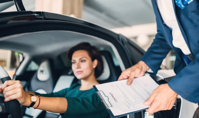 woman tries to decide buying a car from dealership