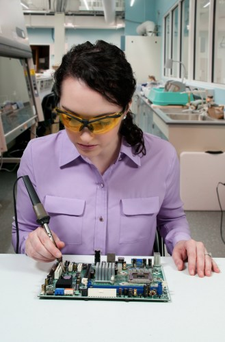 A worker incorrectly holding a soldering iron by the hottest part.
