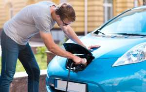 Man charging battery of eco car.