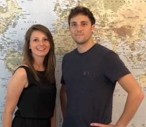 Picture of Camille and Loic behind a world map