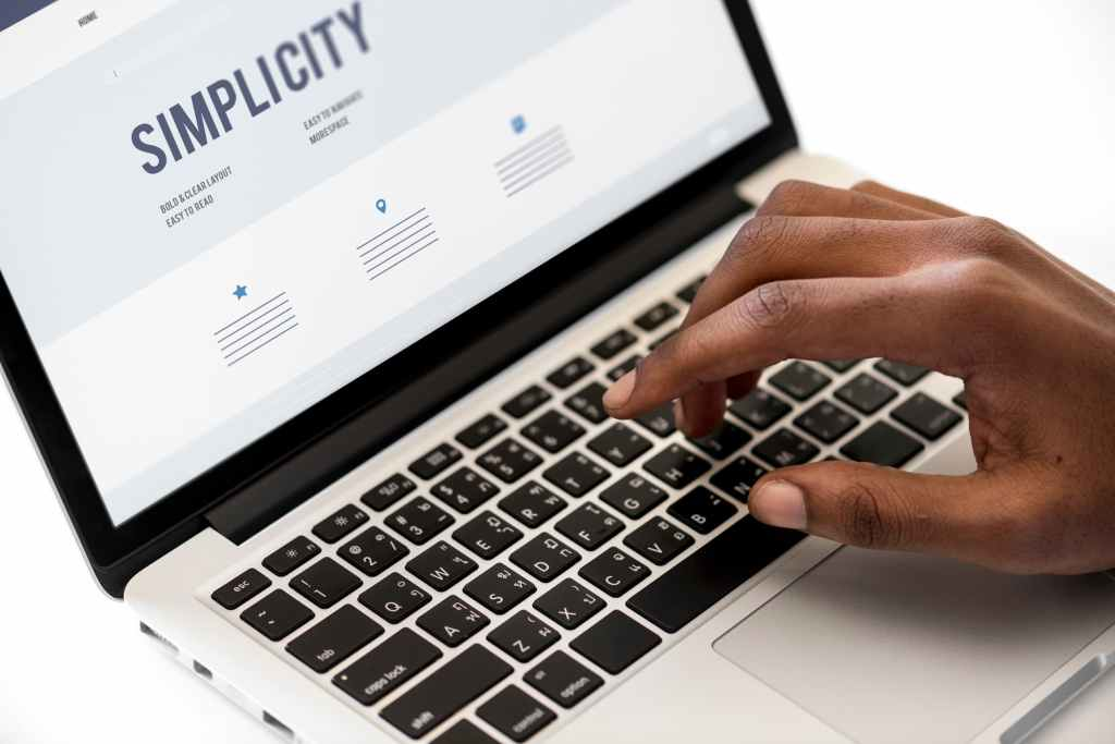 """Woman typing on an a Macbook that displays a """"Simplicity"""" website"""