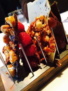 Schokoladetafeln mit Nüssen, Himbeeren, Trauben, Karamell und Kräutermarzipan