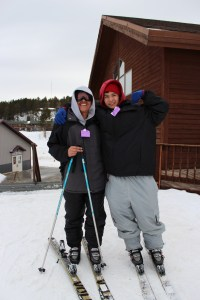 Two boys posing for a picture while on the slopes.