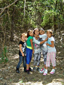 Native American girls hiking through the woods.