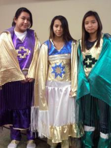 Three Native American girls showing off their beautiful regalia.