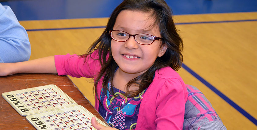 One of St. Joseph's second-grade girls looks up from her bingo cards to smile for the camera.