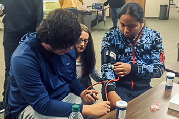 Two St. Joseph's high school students practice monitoring each other's blood pressure under the guidance of an SDUS Pharmacy student.