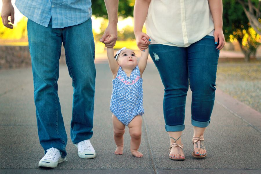 baby walking with parents