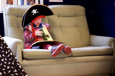 Child reading on couch