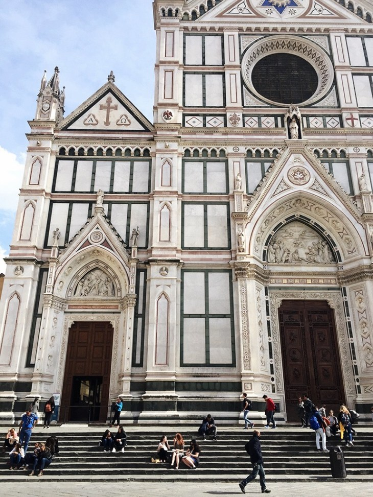 People sitting on the church steps of Santa Croce