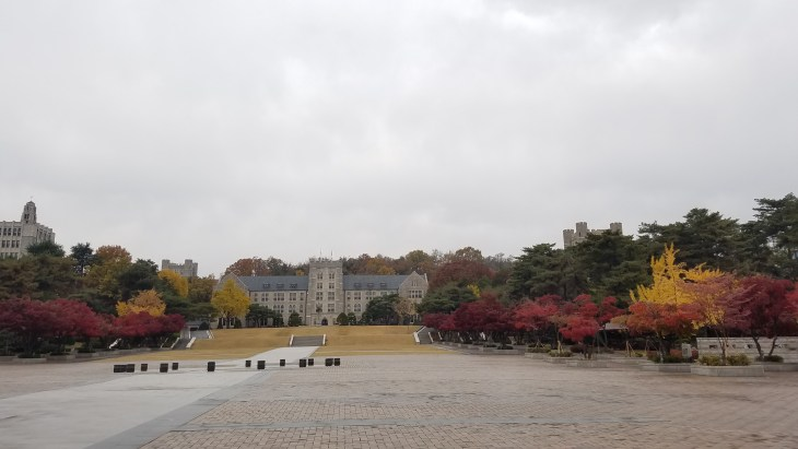 Korean University campus - stone building in background, with multicolored trees