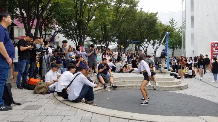 Crowd of people standing and sitting around watching a dancer