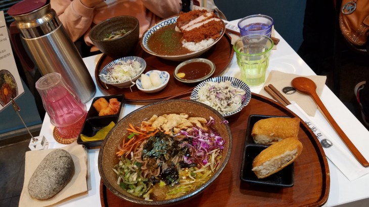 Wooden trays containing several bowls of korean foods
