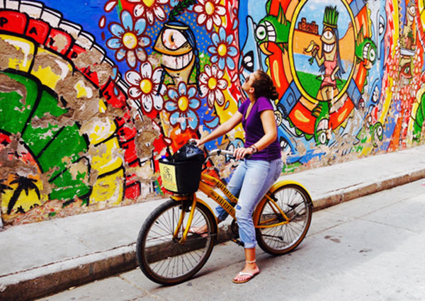 Girl on bike in front of mural