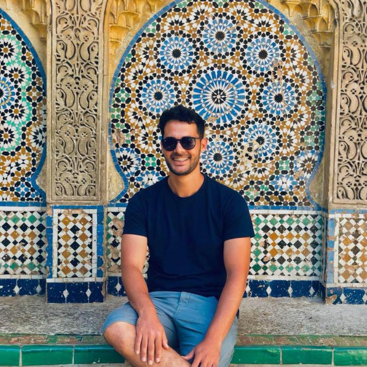 Man sitting in front of Meknes tile wall