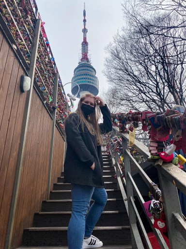 girl standing on stairway lined with colorful locks; seoul tower in the background