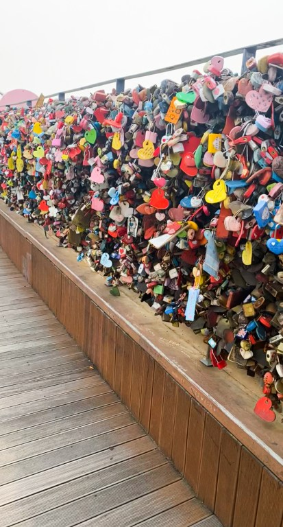 """Bridge with fencing covered in colorful """"love locks"""""""