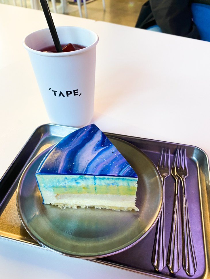 Slice of cake decorated like a galaxy, on a metal tray