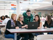 group of students in cafeteria leaning over a laptop