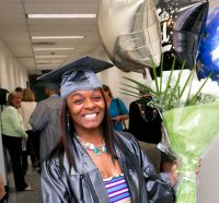 Graduate smiling and holding balloons at graduation