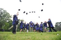 Graduates throwing hats into the air on a field