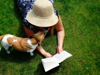 Woman reading a book while dog is nearby