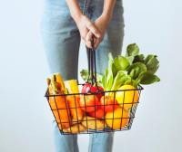 person holding shopping basket full of vegetables
