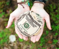 Two open faced hands hold a big ball of crumpled bills in them above a brown and green background of blurry foliage. A metaphoric representation of financial aid such as FAFSA