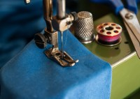 A green sewing machine works on a blue cloth with a spool of red thread sitting next to a pair of scissors