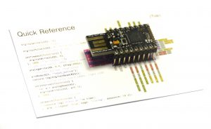 An Espruino USB microcontroller sitting on a reference guide