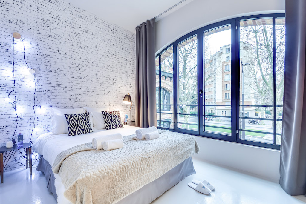 the white bricks wall of the bedroom echoes the exterior's building of this urban loft in south paris by sweet inn