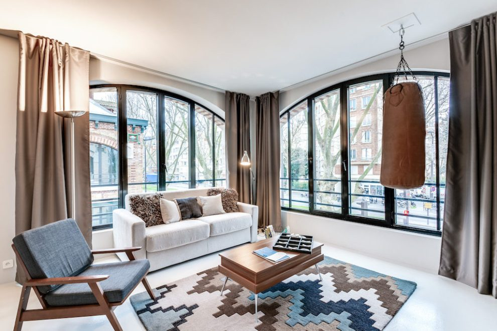 the arched-window adds light in the living-room of this urban loft in south-paris designed by sweet inn