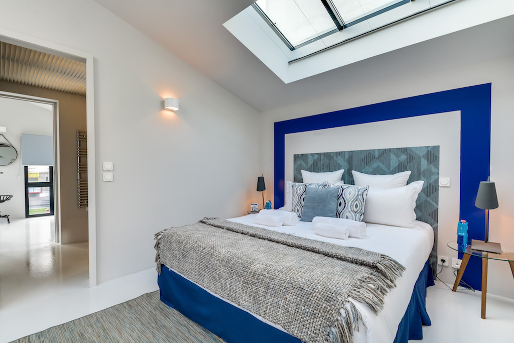 A blue head bed for this double bedroom of this quiet townhouse in the heart of Paris by Sweet Inn