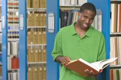 University student studying book in library