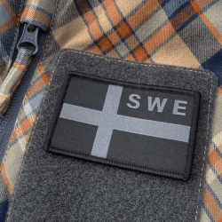 Our black OPS SWE Flag mounted with hook and loop on a plaid shirt