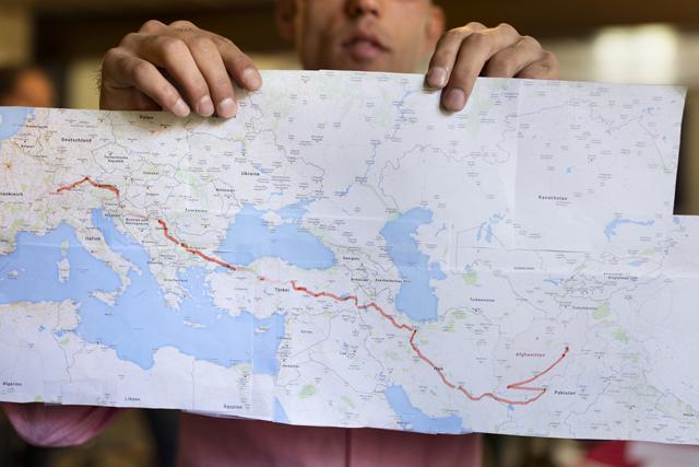 Ein Flüchtling aus Afghanistan zeigt auf einer Karte seinen Weg in die Schweiz. Foto: Gaëtan Bally (Keystone)