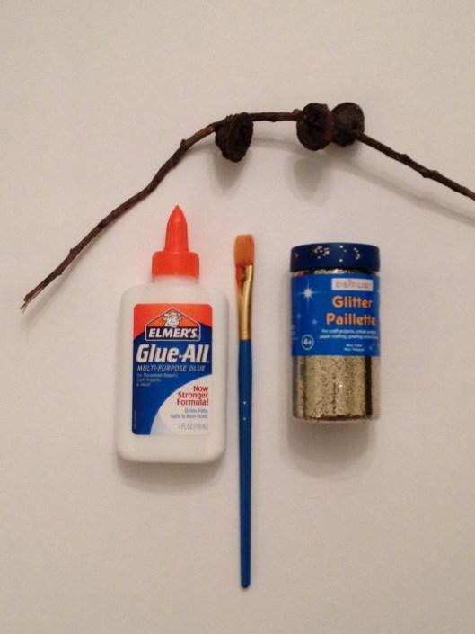 Elmer's glue, paint brush, loose glitter, and eucalyptus acorns.