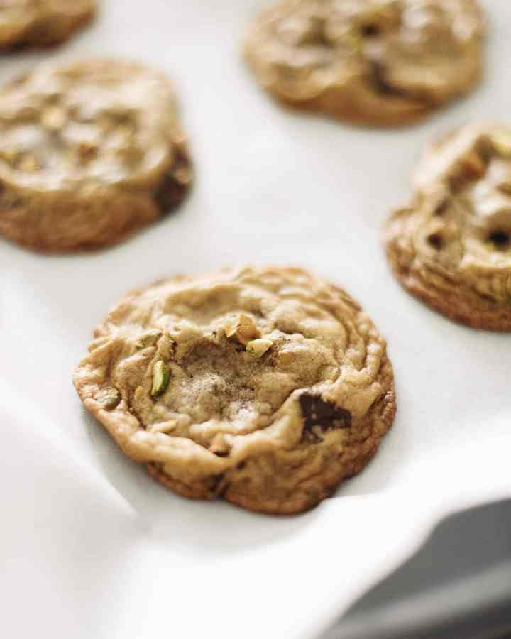 A toasted pistachio dark chocolate cookie on parchment paper