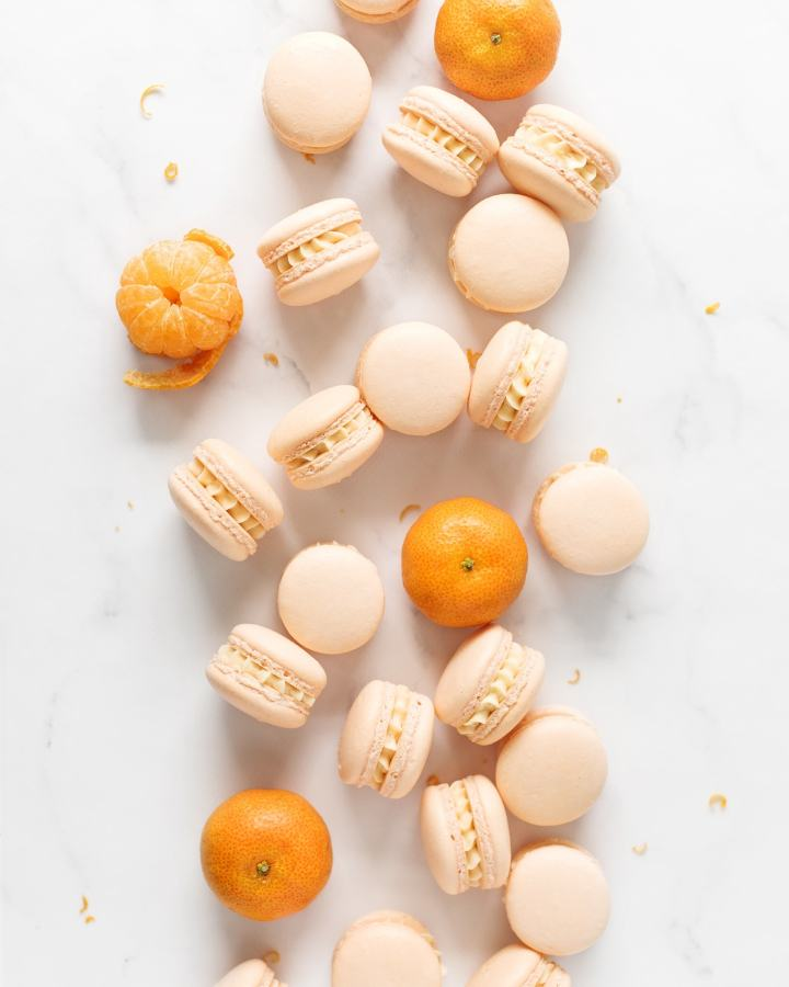 Mandarin orange macarons and mandarin oranges scattered on marble counter